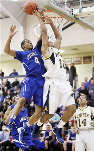 Whitmer's Ricardo Smith, who had 16 points, has his shot blocked from behind by Springfield's Marquan Hodges, who finished with 13 points.