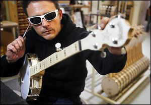 Tony Morbello uses a tuning fork instead of a digital tuner so he can hear the subtle tones while he strings, tunes, and gets the instruments ready to ship at the Deering Banjo Co. Prices for the instruments range from $499 to $30,000.