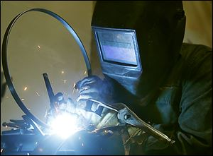 A welder works with the metal tension hoop at the Deering Banjo Co. Deering manufactures each banjo by hand. Greg Deering is the force behind the design and the machinery that builds them.