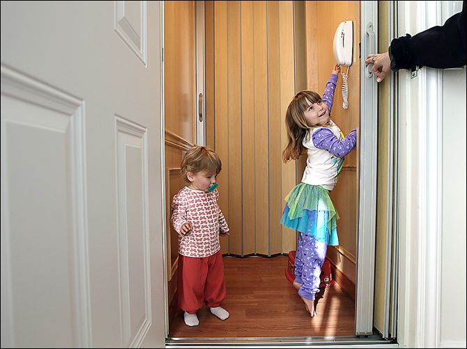 Aden Enzer, 5, right, and her little sister Bennett, 2, use their elevator at home in Los Angeles. Families juggling children, pets and groceries are among those who are adding home elevators.