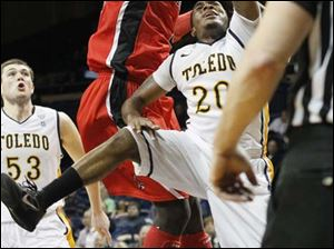 Toledo's guard Julius Brown (20) is blocked on his way to the basket.
