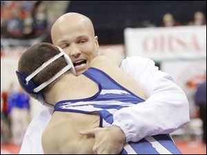 Seth Beard of Napoleon gets a hug from his coach Jason Seiler after defeating Eli Stickley of St. Paris Graham during their Division II 106 pound semi-final match.