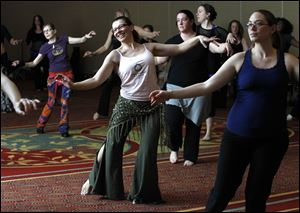Barbara Rocci, second from left in pink sleeveless, and Kristy Windt, right, both of Ann Arbor, learn general belly dancing moves during a seminar at the Grand Plaza in Toledo.