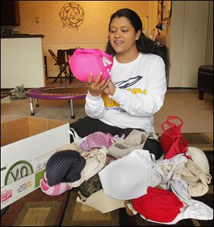 UT grad student Natasha Smet sorts and packs bras in her Toledo apartment for the Free the Girls program.