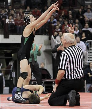 Delta's Jake Spiess celebrates after scoring the winning takedown in overtime on Evan Ulinski of Elmore Woodmore in their Division III 106-pound championship match on Saturday.