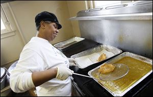 Linda Cross fries fish during the fish fry at Bethel Apostolic Church on W. Bancroft Street in Toledo. The church offers carryout meals as part of its fish fries that are served on the first and third Fridays of each month at its Time Square dinner theater.