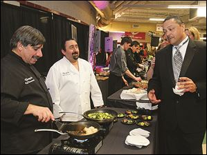 Oliver Frazier, right, chats with George Kamilaris, left, and Joey Amador, center from Georgio's Cafe International, as they prepare food for guests at the American Red Cross' Oscar Night.