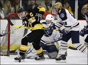 Sylvania Northview's Zander Pryor (19) moves the puck against  St. John's goalie Mike Barrett (29).