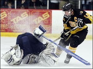 Sylvania Northview's Zander Pryor (19) moves the puck and collides with  St. John's goalie Mike Barrett (29).