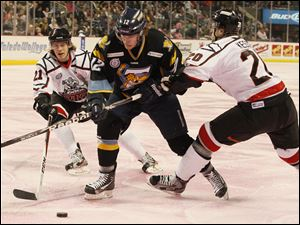 Toledo's Travis Novak, center, pushes past Trenton's Andrew Johnston, left, and Blake Kessel during the first period.