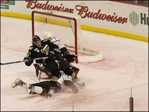 The Walleye's Trevor Parkes is tripped up on his way to the goal during the third period.