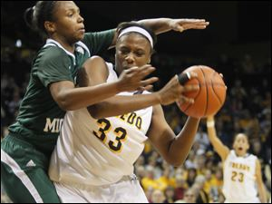 UT's Yolanda Richardson is defended by EMU's Sara Stone in the second half. At right is UT's Inma Zanoguera.