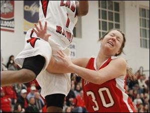 Rogers' junior Sasha Dailey (1) goes in for a layup over Port Clinton's junior Maddie Burris (30).