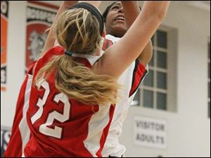 Rogers' junior Marquelle Williams (33) puts up two points over Port Clinton's junior Tiffany Colston (32).