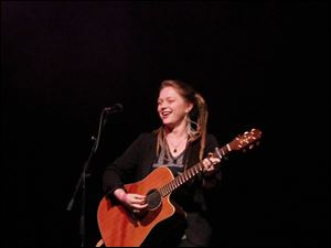 Crystal Bowersox strums the guitar.