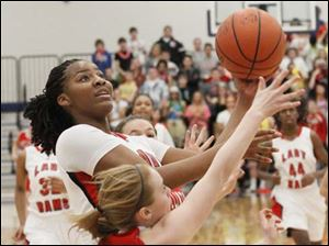 Rogers' junior Tatyana Reynolds (12) goes in for a layup over Port Clinton's freshman Marissa Day (20).