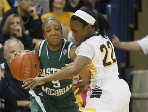 EMU's Iesha Collins is closely guarded by UT's Andola Dortch in the first half.