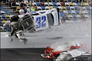 Kyle Larson (32) goes airborne and into the catch fence during a multi-car crash involving Justin Allgaier (31), Brian Scott (2) and others during the final lap of the NASCAR Nationwide Series race Feb. 23 at Daytona International Speedway in Daytona Beach, Fla. Larson's crash sent car parts and other debris flying into the stands injuring spectators.