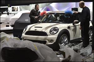 Workers dust a car at the Mini booth during last preparations prior to the opening of the press preview days at the 83nd Geneva International Motor Show in Geneva. The Motor Show will open its gates to the public from Thursday to March 17, presenting more than 260 exhibitors and more than 130 world and European premieres.