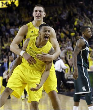 Michigan point guard Trey Burke, front, and forward Mitch McGary celebrate their 58-57 win over Michigan State today Ann Arbor. Trey Burke stole the ball from Keith Appling near midcourt and went in alone for a dunk with 22 seconds remaining, then made another steal in the final seconds to secure the win.