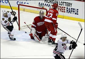 The Blackhawks' Viktor Stalberg, left, celebrates the game-tying goal by teamate Patrick Kane, right, late in the third period. The shot beat Wings' goalie Jimmy Howard, center, and Brian Lashoff.
