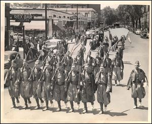 Toledo Pythians shoulder arms in Jubilee Parade. Drill team of Ramadam Temple, Dramatic Order, Knights of Khorassan, swings down Jefferson Ave. with Irving P. Miller, Lambertville, Mich., captain, at far right.  Note the Lorraine Hotel in background on left. Toledo Blade file photo dated May 24, 1948