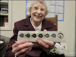 Dona Mae Welch shows the first adding machine she used as Genoa Trinity United Methodist Church's financial secretary, a 'Standard Desk Calcumeter,'stamped with a 1901 manufacture date. Mrs. Welch recently decided to relax a bit and become assistant financial secretary.