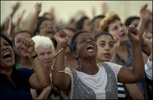 Catholics pray during a Sunday Mass in Sao Paulo.  Catholics around the world attended the first Sunday Masses since Pope Benedict's departure.