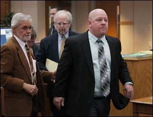 P.J. Kapfhammer, a member of the Oregon school board, right, leaves Oregon Municipal Court with attorneys Jon Richardson, left, and Scott Schwab, following his arraignment today.