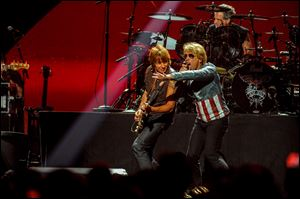 Jon Bon Jovi, right, performs with Richie Sambora at the MGM Grand Arena in Las Vegas. Bon Jovi is going on tour again. This new tour, dubbed Because We Can, after the first single from the new record, will travel the globe through at least July.