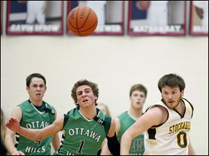 Ottawa Hills' Blake Pappas (1) and  Old Fort's Dalton Perry (0) chase a loose ball.