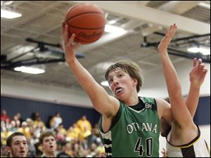Ottawa Hills' RJ Coil (40) pulls in a rebound against  Old Fort's Dalton Perry (0).
