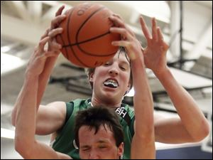 Ottawa Hills' RJ Coil (40) pulls in a rebound against  Old Fort's Cole Davidson (3).