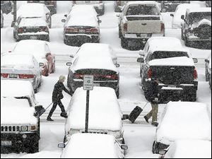 Travelers walk past snow-covered vehicles in the O'Hare International Airport parking lot in Chicago last week.