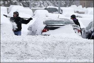 Workers remove snow from cars at an auto dealership today in Bloomington, Minn. left by a storm that is crawling east from the Dakotas and Minnesota toward Chicago which could bring up to 10 inches of snow in some areas.