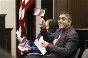 Ahmed Bdair, of South Toledo, right, waves his American flag after receiving his paperwork and taking the oath of citizenship early today during a naturalization ceremony at the Federal Courthouse in downtown Toledo.
