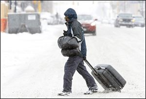 Maury Lawson drags his suitcase through the snow Monday while crossing N.P. Avenue in Fargo, N.D., on his way to the bus depot.