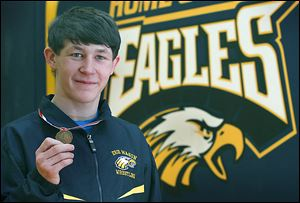 Erie Mason sophomore Logan Griffin holds the medal he won after taking the 112-pound state championship in Division 4. He won the final against Carson City Crystal's Kenneth Dittenber 5-4 in three overtimes.