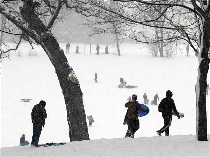 Sledders and snowboarders start amongst the oak trees at the top of the hills today at Randall Oaks Park in the Chicago suburb of West Dundee, Ill.
