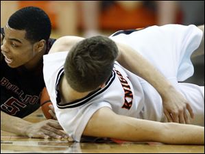 Scott's Chris Harris (5) battles Otsego's Tommy Rodgers (1) for a loose ball.