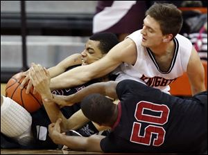 Scott's Chris Harris (5) and Trey Brown (50) battle Otsego's Tommy Rodgers (1) for a loose ball.
