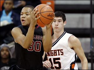 Scott's Bryson Collins (30) looks for an opening against  Otsego's Jerome Griffin (15).