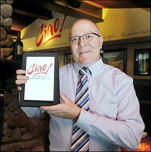 Ciao! Ristorante general manager Terry Kretz holds an Acer tablet menu in use at the restaurant.