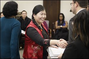 Xiang Lan Geldine of Toledo is all smiles as she receives her papers after a citizenship ceremony.
