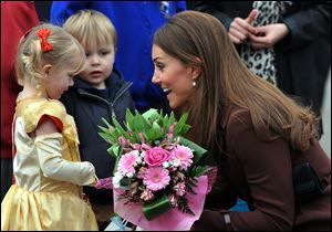 Britain's Catherine, Duchess of Cambridge receives flowers from 3-year old Isobelle Laursen, left, during her visit to Humberside Fire and Rescue Station in Grimsby, north Engalnd, Tuesday.