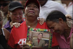 Supporters of Venezuela's President Hugo Chavez cry outside the military hospital where President Hugo Chavez, aged 58, died Tuesday in Caracas.