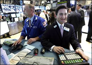 Specialist Christian Sanfillippo, right, smiles as he works at his post on the floor of the New York Stock Exchange.