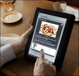 A diner uses an Acer tablet to select an entree at Ciao! Ristorante in Sy