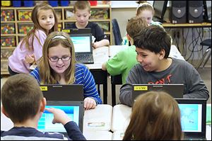 Third graders including Raylynn Nocella, left, and Kane Townsend, right, compete online against students from around the world during the World Education Games. Students at Monroe Road Elementary are participating in the three-day competition.