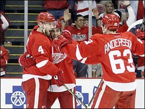 Red Wings defenseman Jakub Kindl, left, celebrates his goal with defenseman Niklas Kronwall, center, and forward Joakim Andersson, right, in the second period.